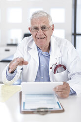 Serious senior doctor at desk discussing patient file - ZEF005997