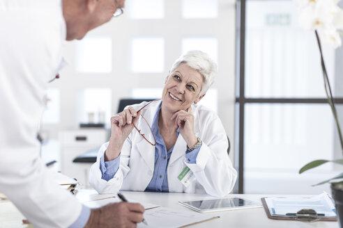 Two doctors talking at desk - ZEF006056
