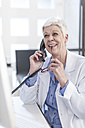 Smiling senior woman in lab coat on the phone - ZEF006058