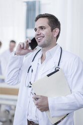 Smiling doctor in hospital on the phone - ZEF006083