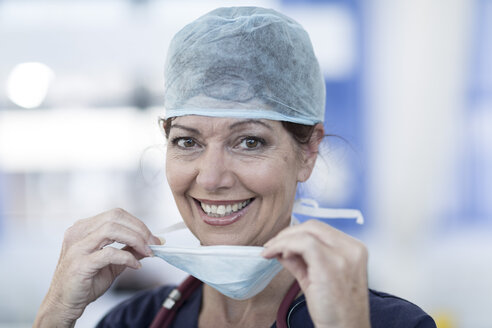 Portrait of smiling doctor in hospital wearing surgical mask - ZEF006117