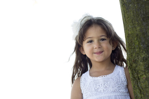 Portrait of smiling little girl leaning on a tree - GDF000813