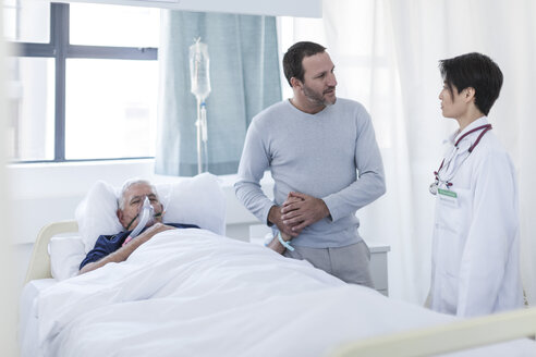 Doctor talking to man visiting patient in hospital - ZEF006764