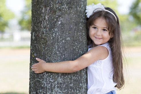 Portrait of smiling little girl hugging a tree - GDF000814