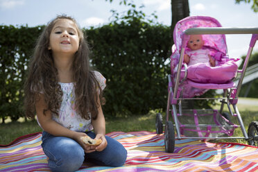 Little girl sitting on a blanket besides her doll buggy - GDF000820