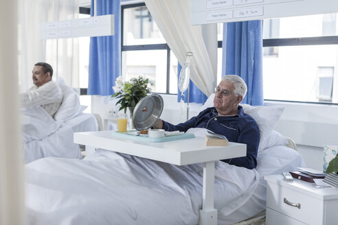 Senior patient in hospital bed looking at meal - ZEF006777