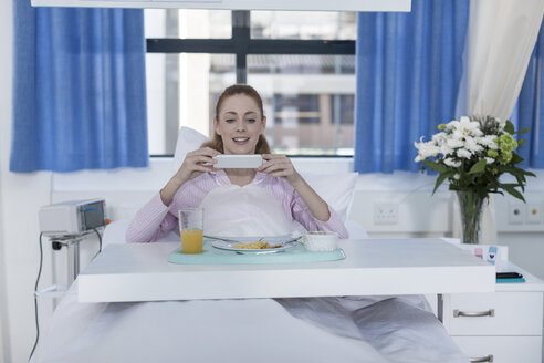 Smiling patient in hospital bed having lunch and looking on cell phone - ZEF006785
