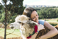 Peru, Cusco, young woman hugging an alpaca - GEMF000275