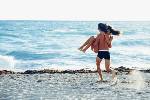 USA, Miami, young man carrying his girlfriend and running into the sea - CHAF000831