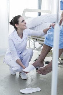 Nurse caring for senior patient in hospital bed - ZEF006839