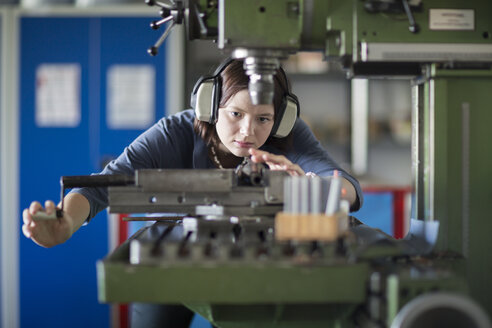 Young woman with ear protectors working at machine - SGF001744