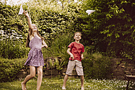 Girl and boy playing with paper planes in garden - MFF001875