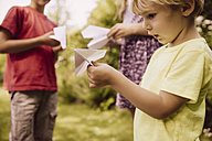 Three children playing with paper planes in garden - MFF001878