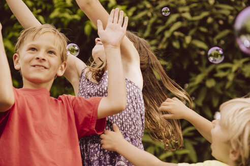 Three children playing with blow soap bubbles in garden - MFF001883