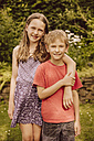 Smiling girl putting arm around brother in garden - MFF001886