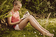 Girl reading a book in garden - MFF001888