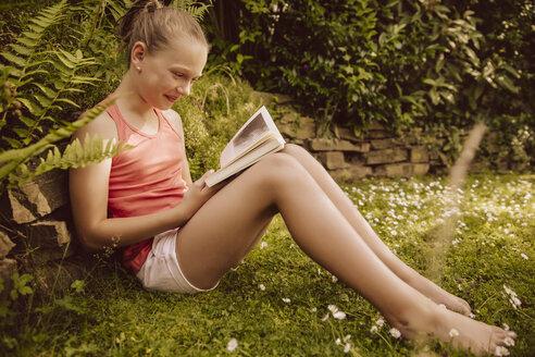 Girl reading a book in garden - MFF001888