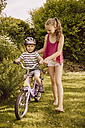 Girl helping little boy riding bicycle in garden - MFF001902