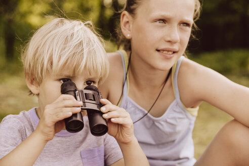 Boy looking through binoculars with his sister - MFF001919