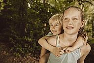 Girl carrying little boy piggyback through a forest - MFF001935