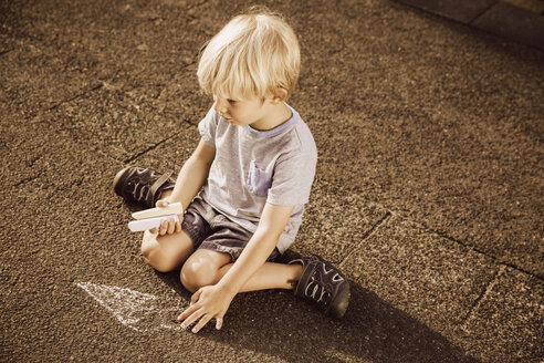 Boy using sidewalk chalk on tarmac - MFF001944