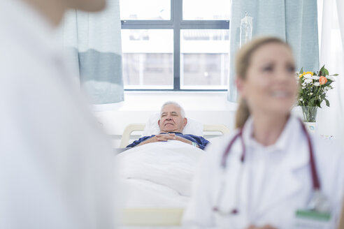 Senior man sleeping in a hospital bed while doctors discussing in the foreground - ZEF006234