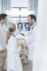 Three doctors with x-ray image in a hospital room - ZEF006238