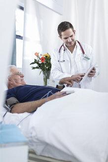 Doctor showing senior man lying in hospital bed something on digital tablet - ZEF006247