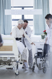 Doctor and staff helping patient with wheelchair in hospital - ZEF006853