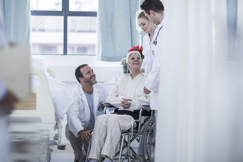 Doctor and staff helping patient with wheelchair in hospital - ZEF006856