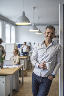 Smiling man in office with colleagues in background - FKF001213