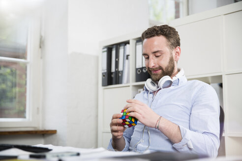 Young man in office at desk with Rubik's cube - FK001341