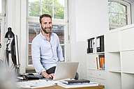 Smiling young man in office at desk using laptop - FKF001239