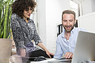 Smiling man and woman in office sharing laptop - FKF001250