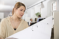 Woman in office looking at plan - FKF001265