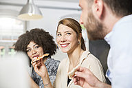 Three colleagues in office eating pizza - FKF001278