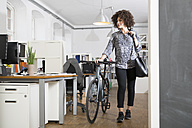 Young woman pushing bicycle in office - FKF001332