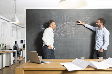 Two businessmen discussing drawing at blackboard - FKF001281