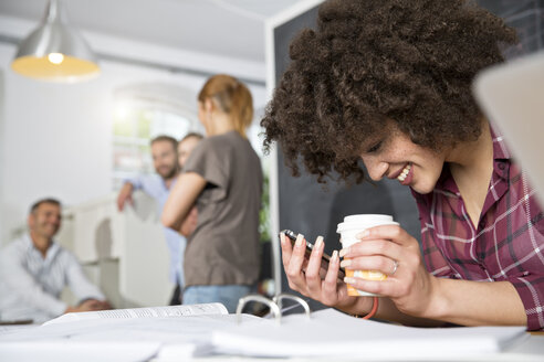 Smiling woman with cell phone and coffee to go in office - FKF001286