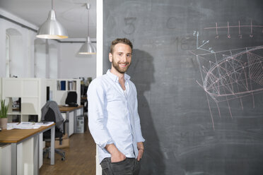 Smiling young man standing at blackboard in office - FKF001287