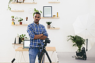 Portrait of young man standing in his photographic studio - EBSF000767