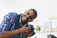 Portrait of smiling young man in his photographic studio - EBSF000773