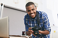 Portrait of smiling young man in his photographic studio - EBSF000776