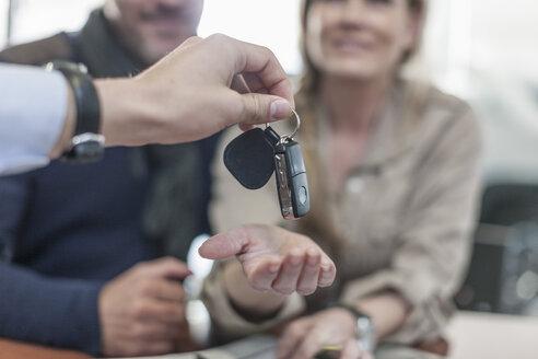 Car dealer giving key to client - ZEF006913