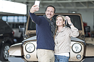 Happy couple at car dealership taking selfie in front of new car - ZEF006922
