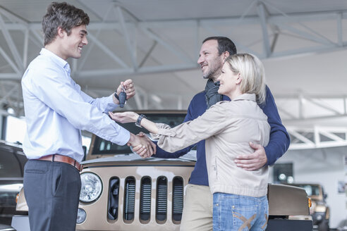 Car dealer giving key to client - ZEF006925