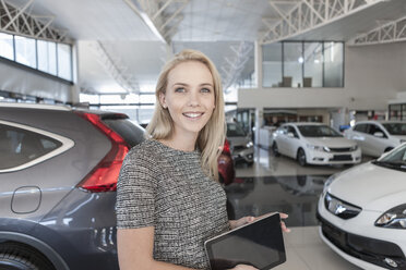 Smiling young woman at car dealership - ZEF006931