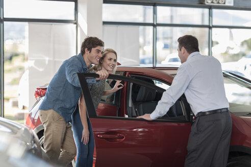 Car dealer showing new car to young couple in showroom - ZEF006932