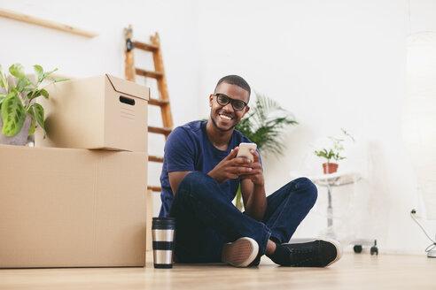 Happy young man sitting beside cardboard boxes having a break - EBSF000805