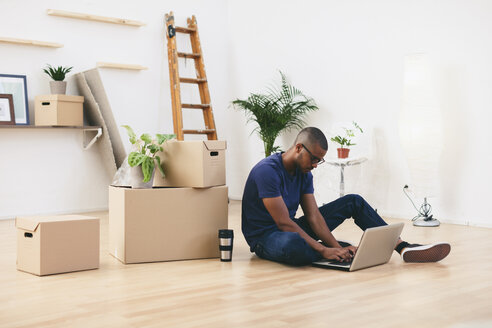 Young man sitting beside cardboard boxes in his new flat using laptop - EBSF000808